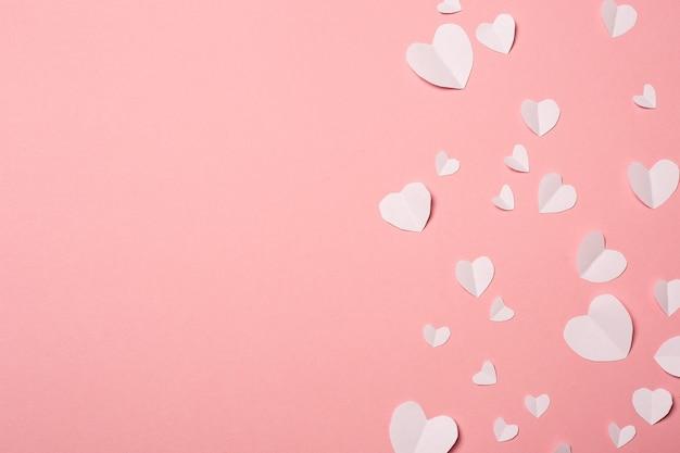 Corazones de papel blanco sobre un fondo rosa. composición del día de san valentín. bandera. vista plana endecha, superior.