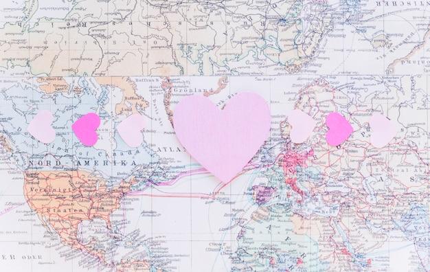 Corazones de papel brillantes pequeños en el mapa del mundo
