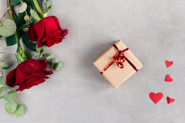 Corazones de papel cerca de la caja actual en envoltura y flores