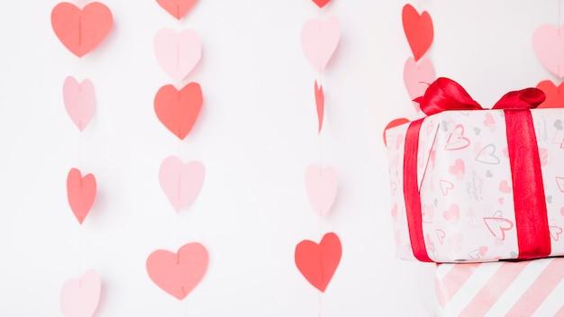 Corazones de papel colgando de una cuerda cerca de cajas de regalo