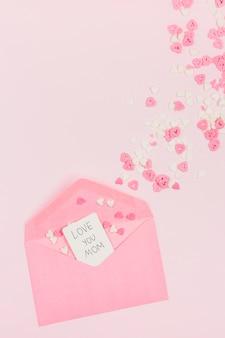 Corazones de papel decorativo cerca de sobre con etiqueta con palabras