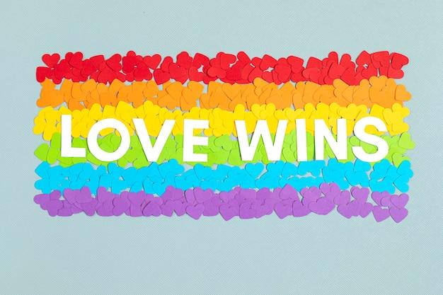 Corazones de papel en forma de bandera con rayas de colores del arco iris, símbolo del orgullo gay lgbt. amor, diversidad, tolerancia, concepto de igualdad.