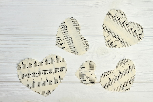 Corazones de papel con notas musicales. conjunto de corazones de papel con notas musicales sobre fondo de madera clara.
