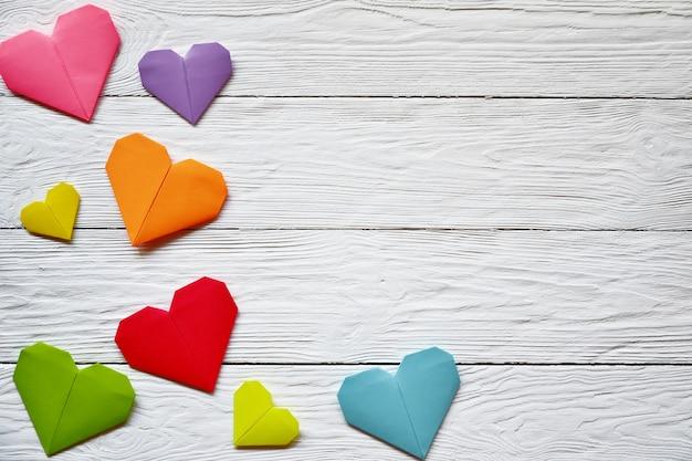 Corazones de papel origami multicolor en una vista superior de madera blanca. brillante día de san valentín