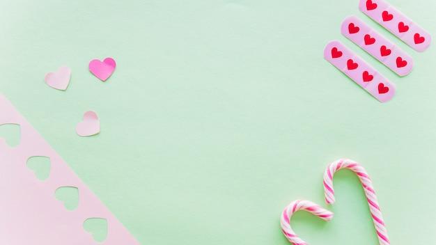 Corazones de papel pequeños con bastones de caramelo.