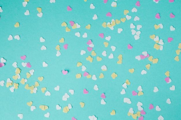 Corazones de papel pequeños esparcidos sobre la mesa.