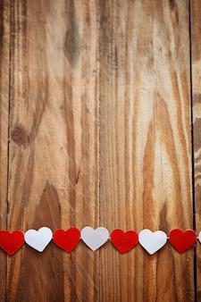 Corazones de papel rojo y blanco en el tendedero en madera backgrou