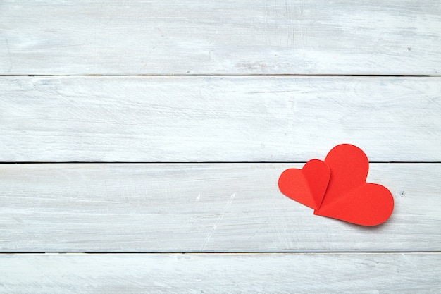 Corazones de papel rojo en madera blanca de san valentín
