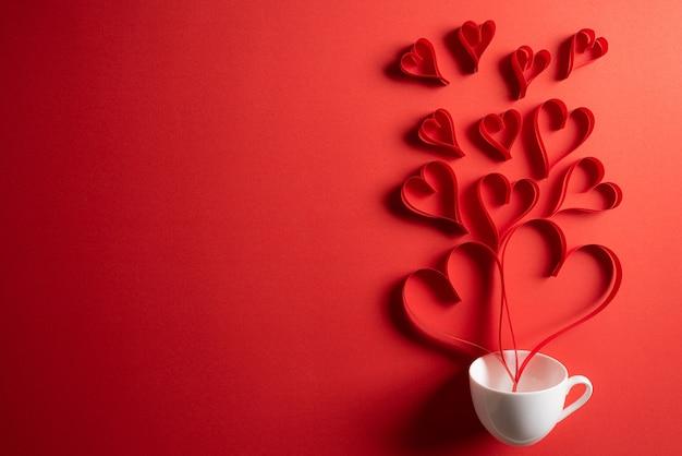 Corazones de papel rojo salpican de la taza de café