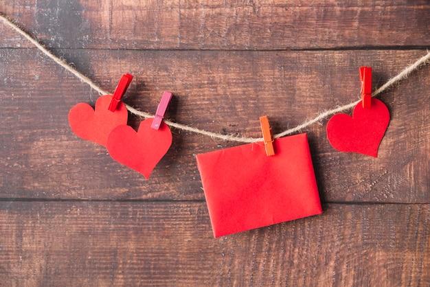 Corazones de papel rojo y sobre con alfileres enganchados en el hilo.