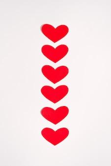 Corazones de papel rojo sobre fondo blanco. tarjeta de vacaciones para el día de san valentín. dia del amor