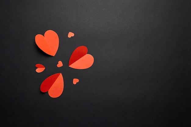 Corazones de papel rojo sobre fondo negro