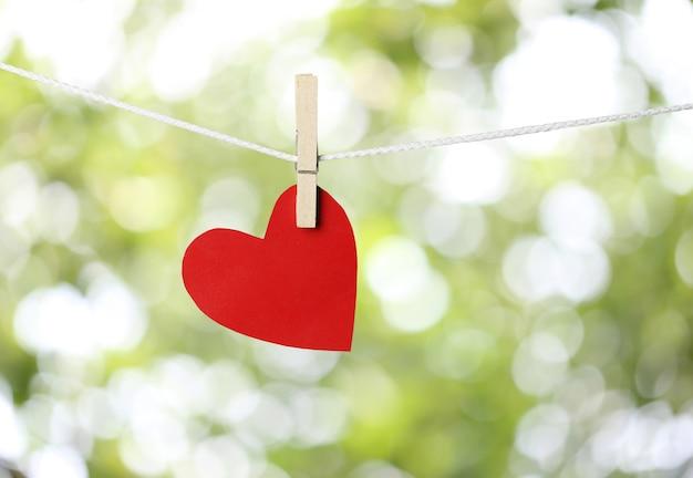 Corazones de papel rojos que cuelgan en la cuerda en concepto del día de san valentín.