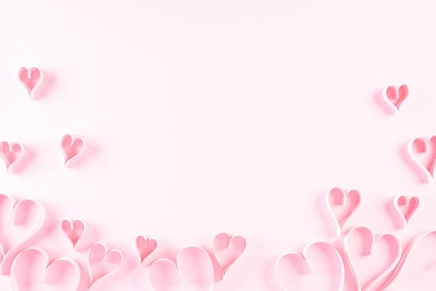 Corazones de papel rosa sobre fondo de papel rosa, amor y concepto de día de san valentín.