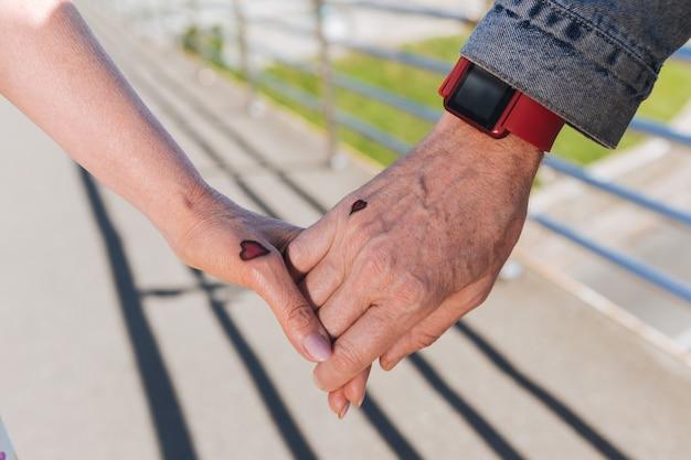 Corazones pequeños. cerca de manos con pequeños tatuajes en forma de corazón que se mantienen juntos