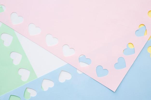 Corazones pequeños sobre papel de colores.