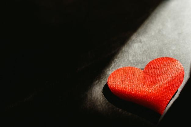 Los corazones rojos aislaron el fondo oscuro iluminado por un rayo de sol para utilizar en el fondo, con mucho espacio vacío de la copia del espacio.