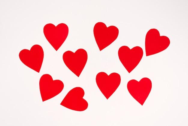 Los corazones rojos están dispersos en un orden caótico sobre un fondo blanco. tarjeta de vacaciones de san valentín