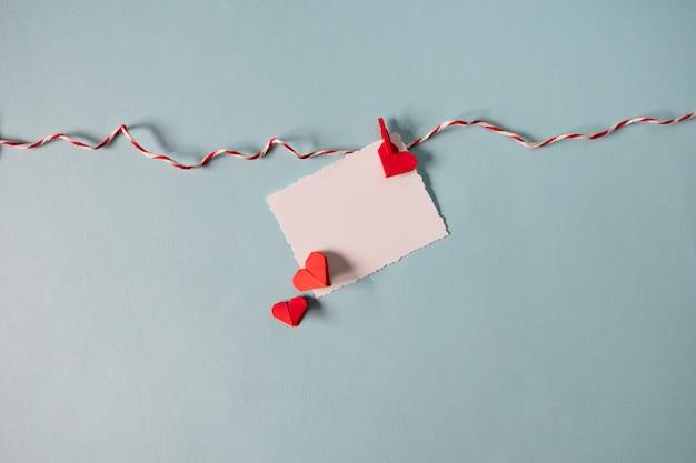 Corazones rojos de origami en cuerda con pinzas para la ropa