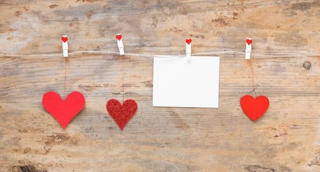 Corazones rojos con papel colgando de una cuerda