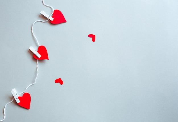 Corazones rojos pegados con alicates en una cinta. concepto de san valentín