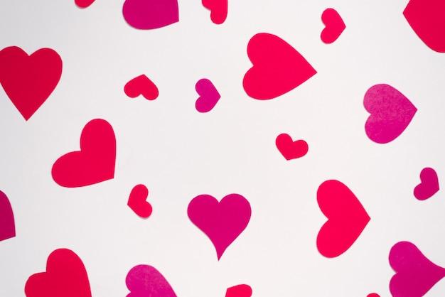 Los corazones rojos y rosados están dispersos en un orden caótico sobre un fondo blanco. tarjeta de vacaciones de san valentín