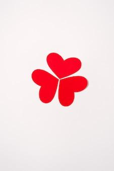 Los corazones rojos y rosados se pliegan en una figura o patrón. tarjeta de felicitación festiva para el día de san valentín. minimalismo y originalidad.