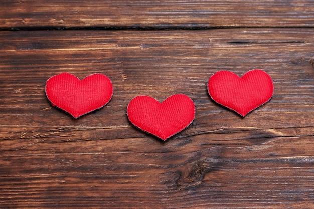 Corazones rojos sobre un fondo de madera oscura.