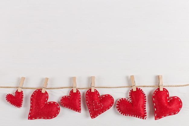 Los corazones rojos son sostenidos por pinzas para la ropa en cuerda de yute, en madera blanca. copia espacio