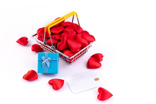 Corazones rojos con tarjeta de crédito y caja de regalo en cesta de la compra, fondo del día de san valentín