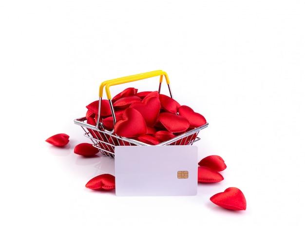 Corazones rojos con tarjeta de crédito en la cesta de compras, fondo del día de san valentín