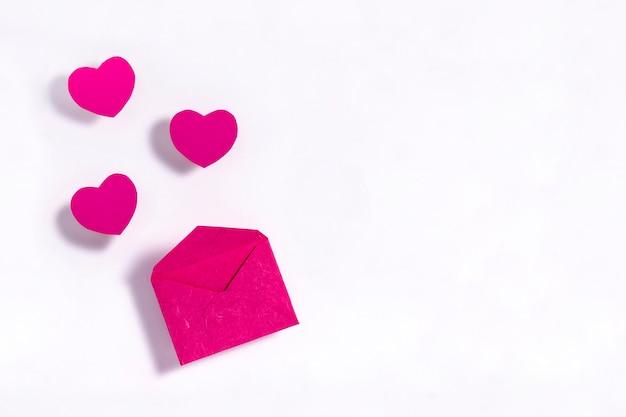 Corazones rosados con sobre en superficie blanca