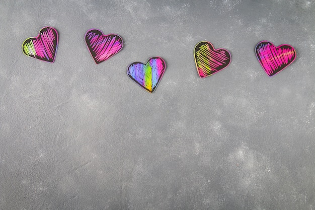 Corazones rosados violetas negros hechos en casa en un fondo concreto gris. el concepto del día de san valentín.