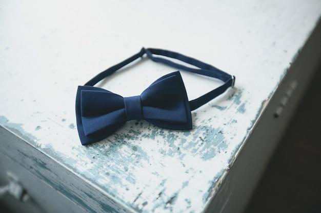 Corbata de lazo azul, un accesorio de moda para un hombre, novio o hombre de negocios, en una vieja mesa de madera en mal estado, que se pela, primer plano. preparando al novio para el día de la boda.