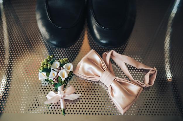 Corbata mariposa, flor en el ojal y zapatos