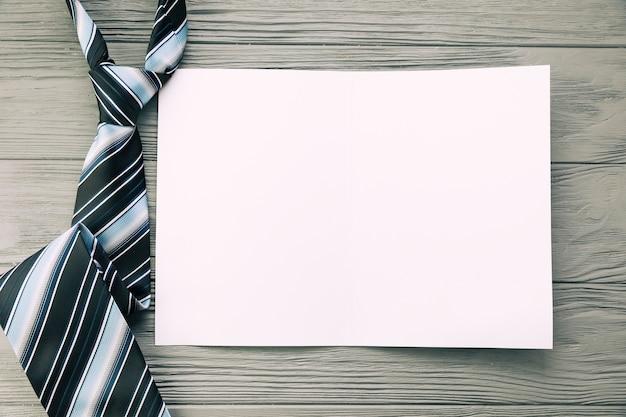 Corbata a rayas y papel sobre la mesa.