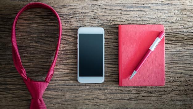 Corbata roja, bolígrafo, cuaderno, teléfono inteligente en mesa de madera