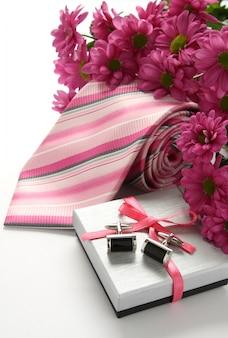 Corbatas y gemelos con flores sobre blanco.