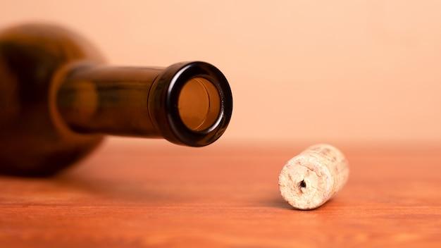 Corcho de vino y mentira botella vacía sobre la mesa.