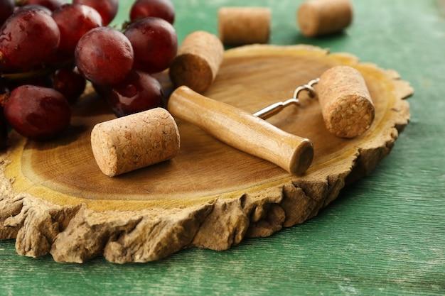 Corchos de vino y barrena con racimo de uvas sobre fondo de madera