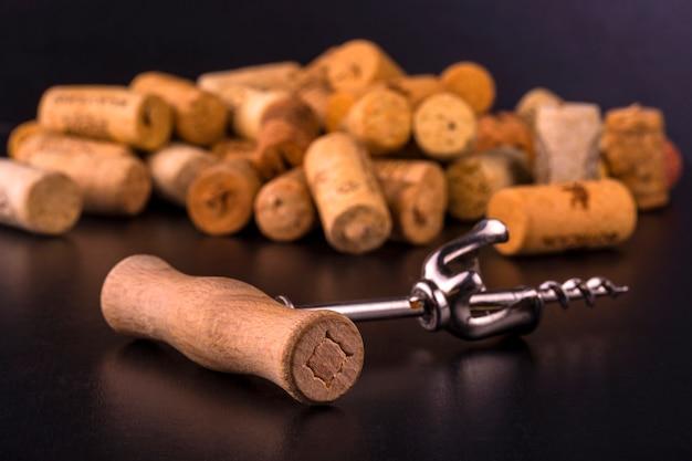 Corchos de vino y sacacorchos en mesa negra