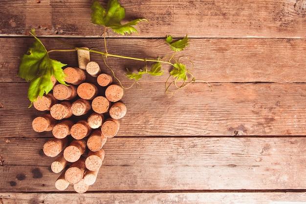 Corchos de vino sobre fondo de madera como forma de uva con hoja verde
