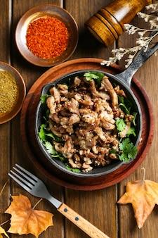 Cordero frito con comino en una olla sobre la mesa de madera
