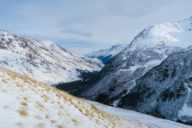 Cordillera de montañas caucásicas en el cielo azul de las nubes. garganta de syltran