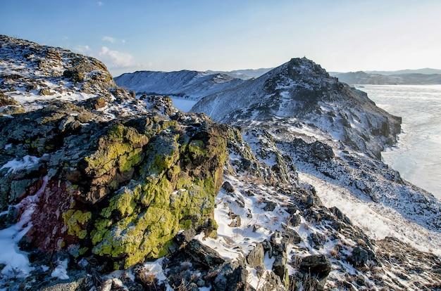 Cordillera con una textura verde cubierta de nieve sobre el lago congelado