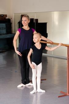 El coreógrafo enseña al niño las posiciones de ballet.