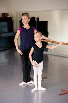 El coreógrafo le enseña al niño las posiciones de ballet.