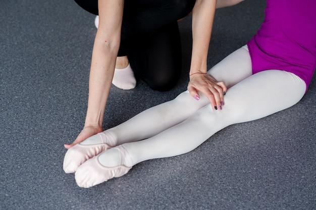 El coreógrafo le enseña al niño la postura correcta.