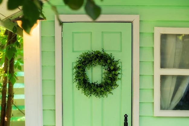 Corona de bienvenida que decora la puerta de entrada a casa puerta de la casa con decoración con hojas corona