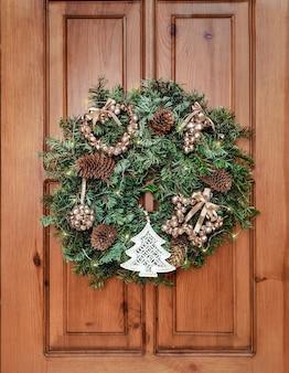 Corona festiva tradicional en la puerta hecha de ramas de abeto y decorada con juguetes navideños